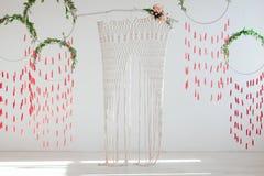Εσωτερικό σχέδιο με την ύφανση και τα λουλούδια Catchers ονείρου άνοιξη με τα πράσινα φύλλα και τις κόκκινες βούρτσες Ψάθινη αψίδ Στοκ φωτογραφία με δικαίωμα ελεύθερης χρήσης