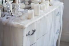 Εσωτερικό σχέδιο του άσπρου δωματίου με τα όμορφα λουλούδια στον εξυπηρετούμενο πίνακα Μεγάλος δημιουργικός κλασσικός καθρέφτης Στοκ Εικόνα