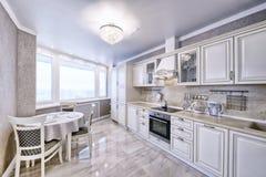Εσωτερικό της άσπρης ξύλινης κουζίνας σε ένα ευρύχωρο διαμέρισμα στα ελαφριά χρώματα Στοκ Εικόνα