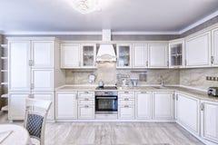 Εσωτερικό της άσπρης ξύλινης κουζίνας σε ένα ευρύχωρο διαμέρισμα στα ελαφριά χρώματα Στοκ Φωτογραφίες