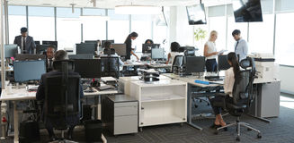 Εσωτερικό του πολυάσχολου σύγχρονου ανοικτού γραφείου σχεδίων με το προσωπικό Στοκ Εικόνες