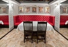 Εσωτερικό δωμάτιο συμποσίου με έναν μεγάλο κόκκινο καναπέ, πίνακας, καρέκλες, mirr Στοκ Εικόνα