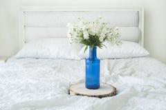 Εσωτερικό δωματίων με τα άσπρα λουλούδια στο μπλε βάζο στο άσπρο κρεβάτι Στοκ Εικόνες