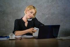 Εταιρικό επιχειρησιακό πορτρέτο της νέας όμορφης και πολυάσχολης γυναίκας με την ξανθή τρίχα που λειτουργεί στο γραφείο φορητών π στοκ εικόνες