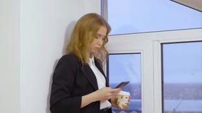 Εταιρικό θηλυκό διευθυντών στο smartphone και κράτημα του μίας χρήσης φλιτζανιού του καφέ κοντά στο παράθυρο φιλμ μικρού μήκους