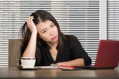 Εταιρικό πορτρέτο της νέας ελκυστικής λυπημένης και τονισμένης ασιατικής κινεζικής εργασίας γυναικών στο γραφείο υπολογιστών γραφ στοκ φωτογραφία