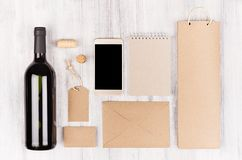 Εταιρικό πρότυπο ταυτότητας για τη βιομηχανία κρασιού με το κόκκινο κρασί μπουκαλιών και wineglass στο μαλακό άσπρο ξύλινο υπόβαθ Στοκ Εικόνες