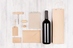 Εταιρικό πρότυπο ταυτότητας για τη βιομηχανία κρασιού με το κόκκινο κρασί μπουκαλιών στο μαλακό άσπρο ξύλινο υπόβαθρο Στοκ φωτογραφία με δικαίωμα ελεύθερης χρήσης