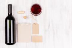 Εταιρικό πρότυπο ταυτότητας για τη βιομηχανία κρασιού με το κόκκινο κρασί μπουκαλιών και wineglass στο μαλακό άσπρο ξύλινο υπόβαθ Στοκ φωτογραφία με δικαίωμα ελεύθερης χρήσης