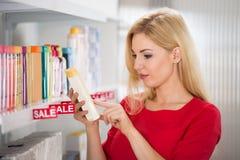 Ετικέτα ανάγνωσης πελατών στο καλλυντικό μπουκάλι Στοκ εικόνες με δικαίωμα ελεύθερης χρήσης