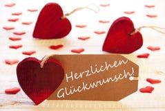 Ετικέτα με πολλούς κόκκινη καρδιά, συγχαρητήρια μέσων Herzlichen Glueckwunsch στοκ εικόνες