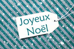 Ετικέτα σε τυρκουάζ χαρτί, Snowflakes, Χαρούμενα Χριστούγεννα μέσων Joyeux Noel Στοκ εικόνες με δικαίωμα ελεύθερης χρήσης
