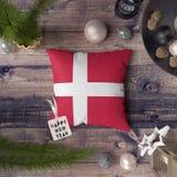 Ετικέττα καλής χρονιάς με τη σημαία της Δανίας στο μαξιλάρι Έννοια διακοσμήσεων Χριστουγέννων στον ξύλινο πίνακα με τα καλά αντικ στοκ εικόνες