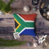 Ετικέττα καλής χρονιάς με τη σημαία της Νότιας Αφρικής στο μαξιλάρι Έννοια διακοσμήσεων Χριστουγέννων στον ξύλινο πίνακα με τα κα στοκ φωτογραφίες