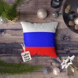 Ετικέττα καλής χρονιάς με τη σημαία της Ρωσίας στο μαξιλάρι Έννοια διακοσμήσεων Χριστουγέννων στον ξύλινο πίνακα με τα καλά αντικ στοκ φωτογραφίες