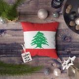 Ετικέττα καλής χρονιάς με τη σημαία του Λιβάνου στο μαξιλάρι Έννοια διακοσμήσεων Χριστουγέννων στον ξύλινο πίνακα με τα καλά αντι στοκ εικόνα
