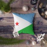 Ετικέττα καλής χρονιάς με τη σημαία του Τζιμπουτί στο μαξιλάρι Έννοια διακοσμήσεων Χριστουγέννων στον ξύλινο πίνακα με τα καλά αν στοκ εικόνες