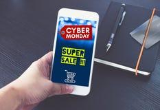 Ετικέττα πώλησης Δευτέρας Cyber με το κάρρο αγορών στην κινητή οθόνη, χέρι χ Στοκ Εικόνες