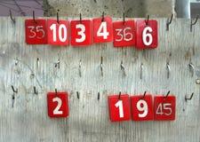 Ετικέττες αριθμών που κρεμούν παλαιό σε έναν ξύλινο Στοκ Φωτογραφία