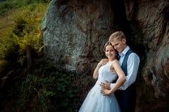 Ευαίσθητο γαμήλιο πορτρέτο Όμορφος νεόνυμφος που αγκαλιάζει μαλακά τη νύφη πίσω στα ηλιόλουστα βουνά στοκ φωτογραφία με δικαίωμα ελεύθερης χρήσης