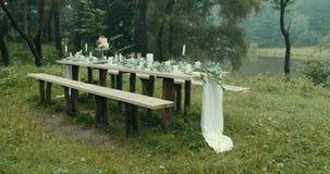 Ευαίσθητο ντεκόρ για την ημερομηνία στο ομιχλώδες μυστήριο ξύλο Καλές διακοσμήσεις: κεριά, φύλλα, λουλούδια και όμορφος two-tiere φιλμ μικρού μήκους