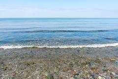Ευγενής κυματωγή θάλασσας σε μια παραλία των χαλικιών, ορίζοντας και μπλε ουρανός, για Στοκ Φωτογραφίες