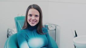 Ευθέα δόντια και ένα άσπρο χαμόγελο εξέταση στον καθρέφτη τα δόντια της απόθεμα βίντεο
