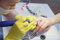 Ευθυγράμμιση των καρφιών και επεξεργασία των καρφιών που χρησιμοποιούν μια ηλεκτρική μηχανή στοκ φωτογραφία