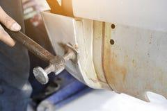 Ευθυγραμμίστε το αυτοκίνητο σωμάτων μετάλλων με το σφυρί στη αυτοκινητοβιομηχανία - αυτόματο β Στοκ Φωτογραφία
