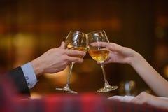 Ευθυμίες! Δύο χέρια με τα ποτήρια του κρασιού - φωτογραφία αποθεμάτων Στοκ Εικόνες