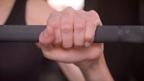 Ευθύς βλαστός κινηματογραφήσεων σε πρώτο πλάνο των νέων ελκυστικών θηλυκών χεριών αθλητών που παίρνουν έτοιμων να ανυψώσει τα βάρ φιλμ μικρού μήκους