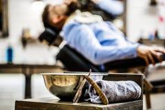 Ευθύ ξυράφι, barbershop, πετσέτα Σαλόνι καταστημάτων κουρέων Κούρεμα ατόμων Άτομο στο σαλόνι barbershop Γενειοφόρο άτομο, γενειάδ στοκ φωτογραφία