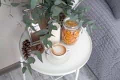 Ευκάλυπτος στο εσωτερικό, καφές πρωινού στον πίνακα στην κρεβατοκάμαρα από το κρεβάτι Στοκ Φωτογραφία