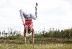 Ευκίνητη νέα γυναίκα που κάνει ένα handstand Στοκ Εικόνα