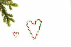λευκό σύνθεσης Χριστο&upsilon Πράσινοι κάλαμοι κλάδων και καραμελών δέντρων έλατου που διαμορφώνουν τις μορφές καρδιών Τοπ άποψη, Στοκ Φωτογραφίες