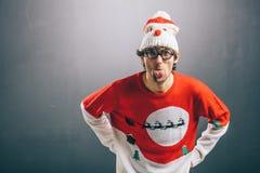 Ευμετάβλητο άτομο στα αστεία ενδύματα Χριστουγέννων που κολλούν έξω τη γλώσσα του στοκ φωτογραφίες