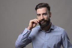 Ευμετάβλητο πορτρέτο του νέου μοντέρνου γενειοφόρου ατόμου που στροβιλίζει mustache και που εξετάζει τη κάμερα Στοκ Φωτογραφίες