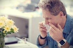 Ευμετάβλητο σκυθρωπό άτομο που έχει μια τρέχοντας μύτη Στοκ Φωτογραφίες