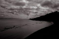 Ευμετάβλητη παραλία, τονισμένος γραπτός, απότομοι βράχοι σκιαγραφιών Στοκ Εικόνα