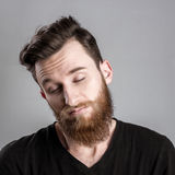 Ευμετάβλητος και λυπημένος νεαρός άνδρας που απομονώνεται στο γκρίζο backround Στοκ Φωτογραφίες