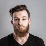 Ευμετάβλητος και λυπημένος νεαρός άνδρας που απομονώνεται στο γκρίζο backround Στοκ φωτογραφία με δικαίωμα ελεύθερης χρήσης