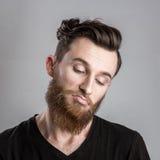 Ευμετάβλητος και λυπημένος νεαρός άνδρας που απομονώνεται στο γκρίζο backround Στοκ Φωτογραφία