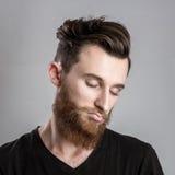 Ευμετάβλητος και λυπημένος νεαρός άνδρας που απομονώνεται στο γκρίζο backround Στοκ Εικόνες