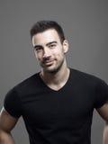 Ευμετάβλητο πορτρέτο του βέβαιου νέου αρσενικού προτύπου ικανότητας χαμόγελου στο κενό μαύρο πουκάμισο στοκ εικόνες