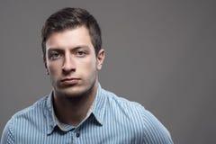 Ευμετάβλητο δραματικό πορτρέτο του σοβαρού νεαρού άνδρα στο μπλε πουκάμισο που εξετάζει το camer Στοκ Φωτογραφίες