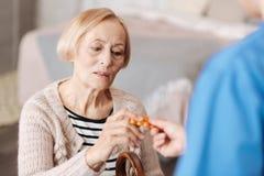 Ευπαθής εύθραυστη ώριμη γυναίκα που έχει τα χάπια ορισμένων στοκ εικόνα
