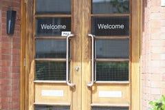 Ευπρόσδεκτο σημάδι εισόδων χαιρετισμού στις διπλές ξύλινες βερνικωμένες πόρτες στο χώρο εργασίας γραφείων στοκ εικόνες