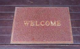 Ευπρόσδεκτος τάπητας doormat στο πάτωμα Στοκ Φωτογραφία
