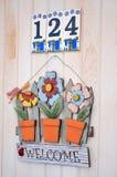 Ευπρόσδεκτο σημάδι με τα ζωηρόχρωμα λουλούδια μετάλλων στοκ εικόνα