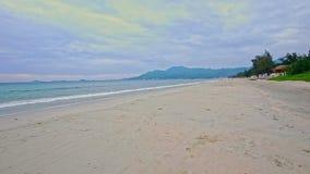 Ευρέως πολύ άσπρη κυματωγή κυμάτων παραλιών άμμου ενάντια στο νεφελώδη μπλε ουρανό απόθεμα βίντεο